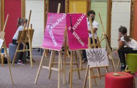 Na zdjęciu uczestnicy spotkania Dyskusyjnego Klubu Książki dla Dzieci oraz pani bibliotekarka. Pani czyta dzieciom książkę.